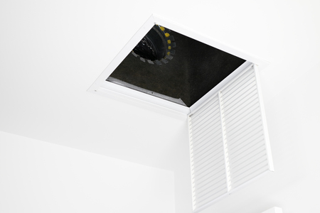 White square ceiling furnace air vent grate open, showing inside the duct. Metal air intake grate open and hanging from the ceiling showing view of inside the HVAC system.