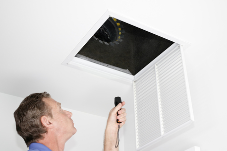 Male looking up into a ceiling air intake duct with a flashlight checking for maintenance. Person with a flashlight examining with a square opening of a home HVAC system  Stock Photo