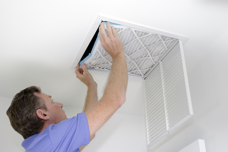 Guy placing into a square ceiling intake vent a clean white and blue air filter. As regular monthly maintenance a male puts in a new air filter in his ceiling air return. Stock Photo