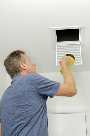 Homeowner looking into a small air duct searching for and dirt and examining the condition. Male examining the cleanliness of a small home HVAC air duct. Stock Photo