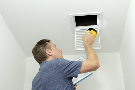 Man inspecting air ducts shining a flashlight through a small square ceiling vent into ducting pipes. Mature male examining the condition of air ducts at home.