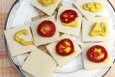Snack of crackers with red jalapenos, cheese and mustard. Appetizer of cheese mustard pepper slices. Stock Photo