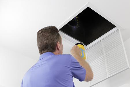 Older male with a yellow flashlight examining HVAC ducts in a large square vent. Male technician looking over the air ducts inside a home air intake vent. Stock Photo