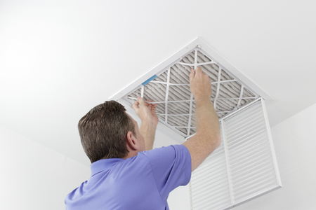 Caucasian male removing a square pleated dirty air filter with both hands from a ceiling air duct. Guy taking out an unclean air filter from a home ceiling air vent. Archivio Fotografico