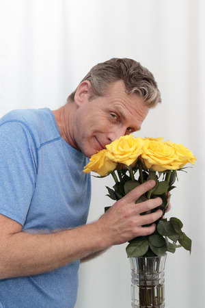 Mature male holds a dozen yellow pink roses happy. Man smilies smelling a bunch of aromatic roses. Middle-aged man holds a yellow pink roses bouquet, thankful for the aroma smiling at the viewer. Stock Photo