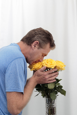 Male holding and smelling a bunch of yellow roses. Bouquet of yellow roses being held and smelled. Dozen yellow roses arrangement with tiny pink streaks being embraced by a mature man who is appreciating their scent.