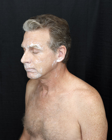 Male wearing a light bentonite clay treatment mask Thin bentonite clay face treatment worn by a guy. Thin white bentonite clay beauty treatment of mature shirtless man on black cloth curtain background