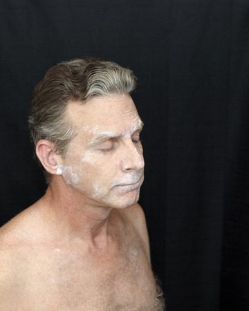 Wearing thin bentonite clay mask beauty treatment. A man wearing a liquid bentonite clay face mask. Sparse bentonite clay face mask beauty treatment on shirtless mature white male on black background.
