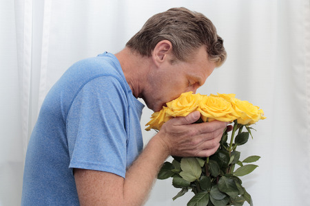 Mature man with his face in a yellow roses bunch. Yellow roses being held, smelled by an older man. One male sniffing a dozen yellow roses with tiny pink spots while holding them close up to his face