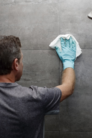 Man cleaning a gray tile bathroom shower wall with a wet cloth while wearing a protective glove. Gray tile bathroom shower wall being cleaned with a cloth rag by a man wearing a cleaning glove. Stock Photo