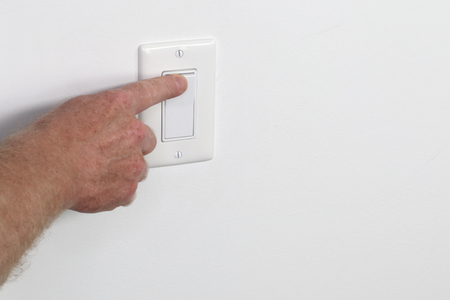 One adult male hand pressing a light switch panel. One flat white panel light switch being turned on Male hand pressing on a flat white wall switch panel from the left to turn on the light in a room. Stock Photo