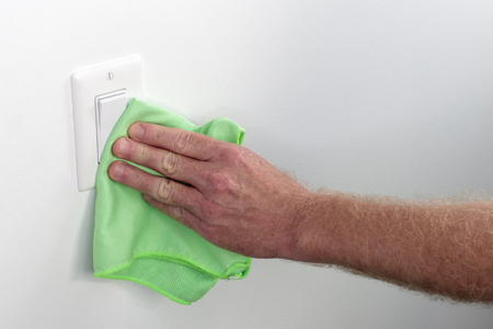 Persons hand wiping a wall white light control. Inside white wall light switch cleaned with a cloth. Indoor flat white light switch being cleaned by a hand with a rag as part of house cleaning chores.