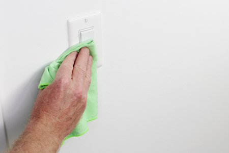 White panel light control cleaning by hand cloth. Male hand dusting light switch with cleaning cloth Flat white light switch control being dusted and cleaned with a green cloth by a caucasian male hand Stock Photo