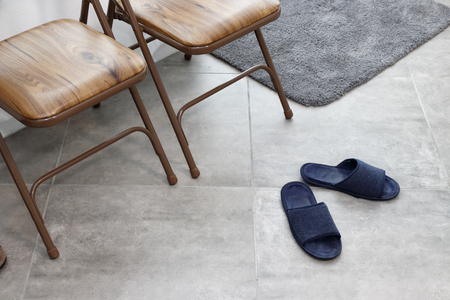 Blue pair of slippers in the entry way of a home. Indoor entrance chairs and slippers of an office. Gray tile entry floor of a home office with two chairs, rug and a pair of blue slippers in the day.
