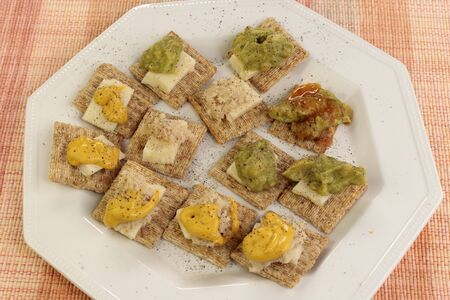Baked whole wheat crackers topped with cheddar cheese, guacamole, horseradish, mustard and hot sauce on a plate. Cheddar cheese, mustard, spicy guacamole and horseradish variety on wholewheat wafers.