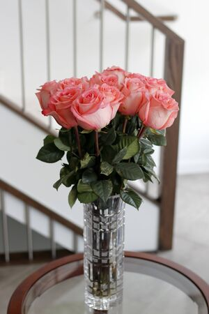 Beautiful darker pink rose flowers with dark green leaves in a glass crystal vase on a living room side table. Pink roses flower bouquet in a clear tall crystal vase on a round table near a stairwell. Stockfoto