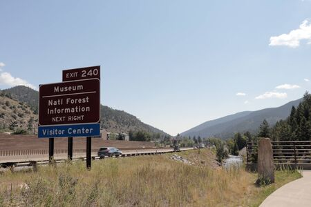 Idaho Springs, CO, USA - August 9, 2018: Highway exit 240 sign for Museum, Natl Forest Information and Visitor Center near Clear Creek Greenway. Exit 240 sign as seen from Clear Creek Greenway trail.