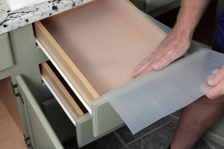 Adult white man inserting a clear thick plastic drawer liner with lines in it into a bathroom drawer. Closeup of adult guy lining a green wood and white bathroom drawers with plastic protection. Banco de Imagens