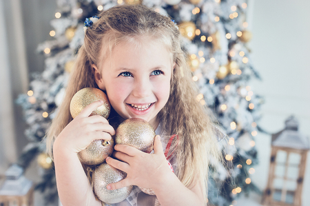 girl decorating christmas tree with balls at home. winter holidays and people concept. Merry Christmas and Happy Holidays 版權商用圖片
