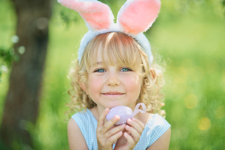 Cute funny girl with Easter eggs and bunny ears at garden. easter concept. Laughing child at Easter egg hunt. Child in park with eggs, spring concept Imagens