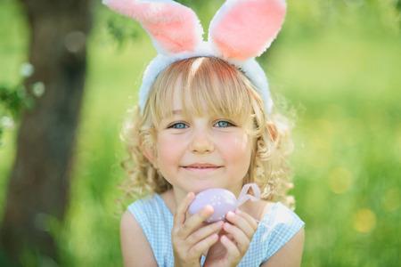 Ragazza carina e divertente con uova di Pasqua e orecchie da coniglio in giardino. concetto di pasqua. Bambino che ride alla caccia alle uova di Pasqua. Bambino nel parco con uova, concetto di primavera Archivio Fotografico