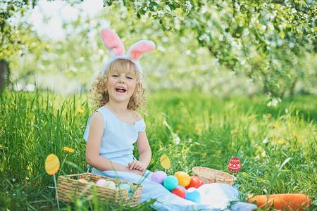 Nettes lustiges Mädchen mit Ostereiern und Hasenohren im Garten. Ostern Konzept. Lachendes Kind bei der Ostereiersuche. Kind im Park mit Korb voller Eier, Frühlingskonzept