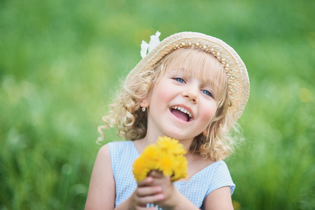 Little girl 5 years old sniffing a dandelion. girl sniffing flowers of apple orchard. garden with flowering trees. Happy childhood. Allergy season, insects. Girl collects dandelions bouquet for a wreath in meadow of orhard.