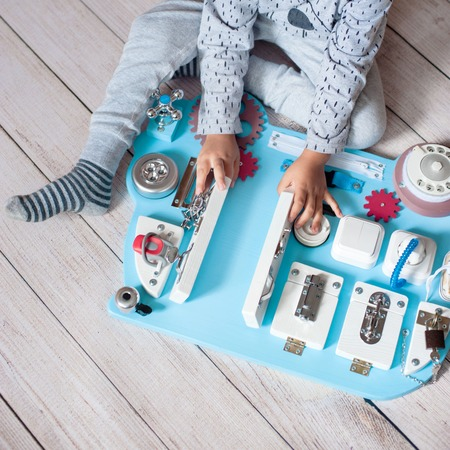 cute toddler baby playing with busy board at home. busy-board for For children. childrens educational toys. Wooden game board. DIY busyboard 写真素材
