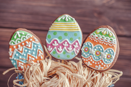 gingerbread cookie in the form of color eggs in blue bucket on wood background.