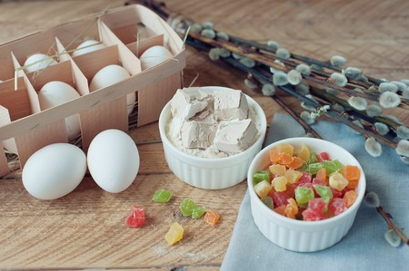 Ingredients for baking Easter cake - eggs, milk, flour, candied fruit, yeast on wooden background