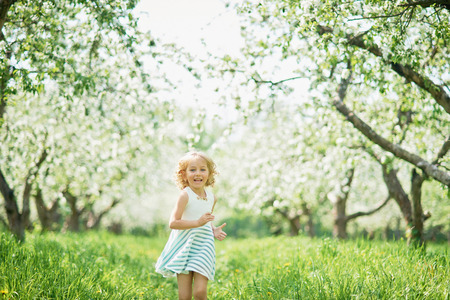 girl sniffing flowers of apple orchard. garden with flowering trees. Allergy season