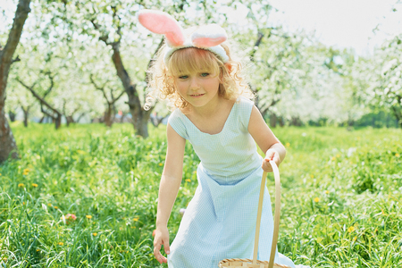 Cute funny girl with Easter eggs and bunny ears at garden. easter concept. Laughing child at Easter egg hunt. Child in park with basket full of eggs, spring concept 스톡 콘텐츠