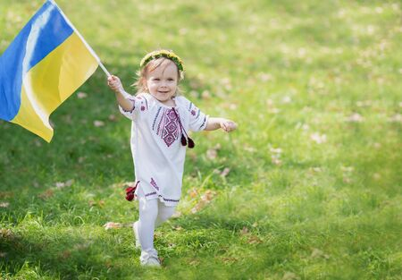 Child carries fluttering blue and yellow flag of Ukraine in field. Ukraines Independence Day. Flag Day. Constitution day. Girl in traditional embroidery with flag of Ukraine