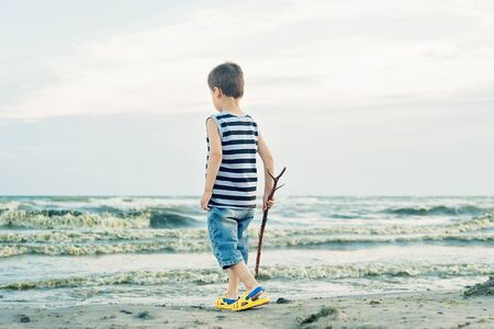 Boy drawing on sand at seaside. Child drawing sand by imaginary on beach for learning. Happy childhood. summer vacation at sea or ocean Stock Photo