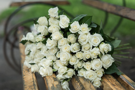 close-up of a huge bouquet of white roses on wooden bench. background of the many roses wedding, the day of St. Valentine. Copy space