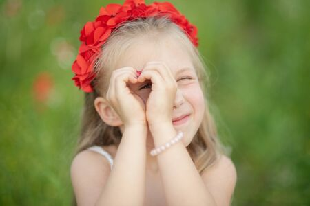 little ukrainian girl looking through heart gesture made with hands in summer green park. Gesture of love by pretty young child in poppy field.