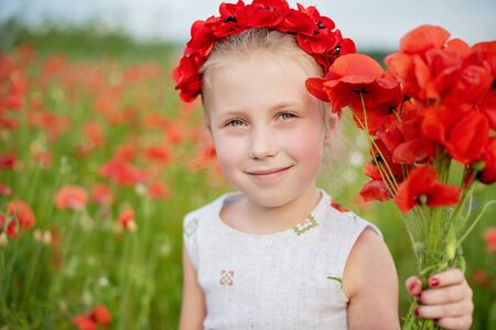 Ukrainian Beautiful girl in vyshivanka with wreath of flowers in a field of poppies and wheat. outdoor portrait in poppies. girl in embroidery Imagens