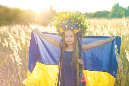 Girl carries fluttering blue and yellow flag of Ukraine in field. Ukraines Independence Flag Day. Constitution day. 24 August. Patriotic holiday.