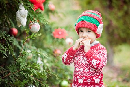 Half-length portrait of a little boy in elf hat and red sweater eating a bun near christmas tree outside