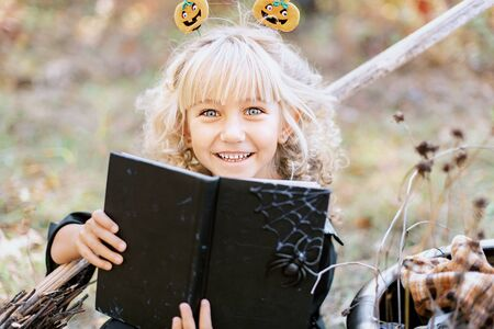 Beautiful girl witch. little girl in witch costume celebrate Halloween outdoor and have fun. Kids trick or treating