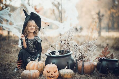 Beautiful girl witch. little girl in which costume celebrate Halloween outdoor and have fun. Kids trick or treating. girl witch with magic Book of spells.
