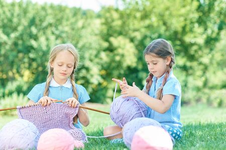 Child sitting on green grass and knitting sweater with needles on summer day. Knitting as a hobby. Accessories for knitting. Copy space Archivio Fotografico