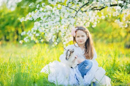 Smiley girl with a little goat sitting in the green grass in a flowering apple garden