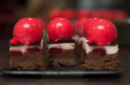 French mousse cakes with mirror glaze. Modern european dessert. Preparation of tasty mousse cake. cooking, baking and confectionery concept