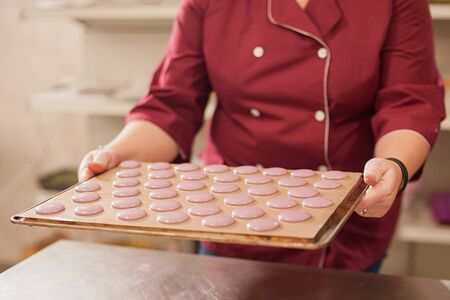 Process of making macaron macaroon, french dessert, squeezing the dough form cooking bag. Food industry, mass or volume production.