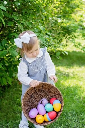 Child play at Easter egg hunt Little toddler girl playing with animal in garden. Cute funny girl at garden. easter concept.