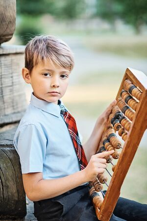 Boy with large abacus. Thoughtful schoolboy using a maths abacus calculation