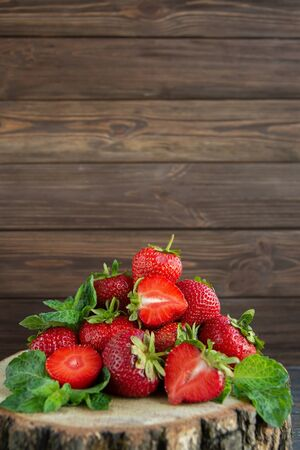 Heap of ripe strawberries on wooden table on blurred background. Organic Berries Closeup. Red, juicy macro photo. Selective focus. Fragaria. Rich in Vitamins, Antioxidants, and Folic Acid. copy space