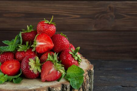 Heap of ripe strawberries on wooden table on blurred background. Organic Berries Closeup. Red, juicy strawberries macro photo. Selective focus. Fragaria. Rich in Vitamins, Antioxidants, and Folic Acid Banco de Imagens