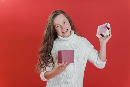 Happy excited child holding Birthday gift box. Child giving present on red vivid color background. christmas and people concept. black friday, cyber monday sale shopping. international childrens day